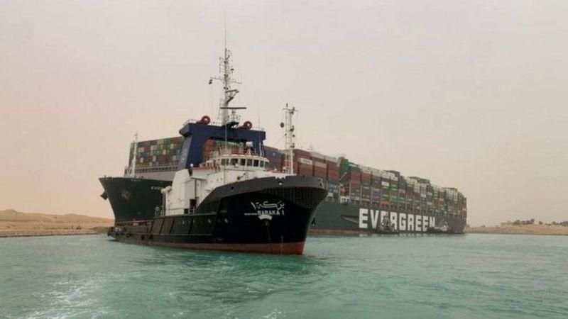 قاطرات جر وحفارات في قناة السويس تستتخدم  لإعادة تعويم السفينة الجانحة في فناة السويس